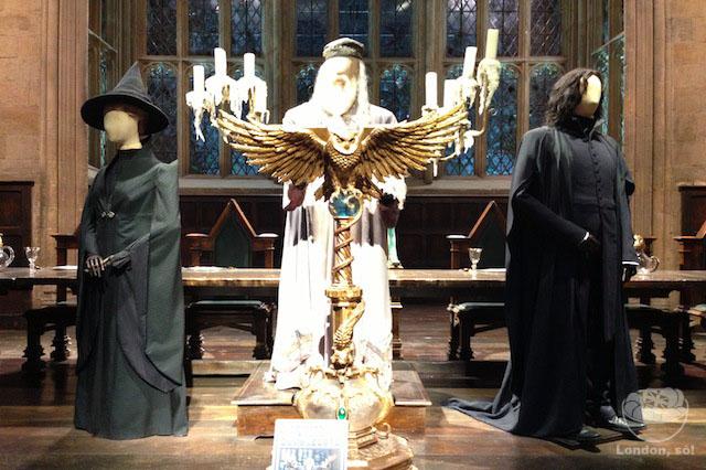 Figurinos dos professores Dumbledore, Snape e Minerva no palco do salão.