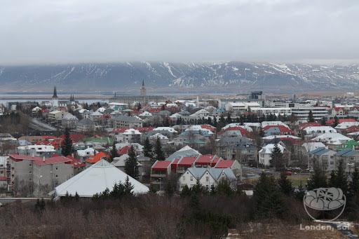 Vista do alto de Reykjavík com suas casinhas coloridas e as montanhas cheias de gelo.