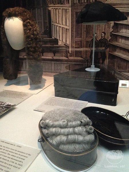 As perucas usadas pelos juízes expostas na galeria de trajes legais.