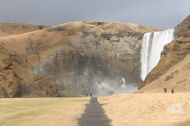 O arco-íris de levinho à esquerda da foto.